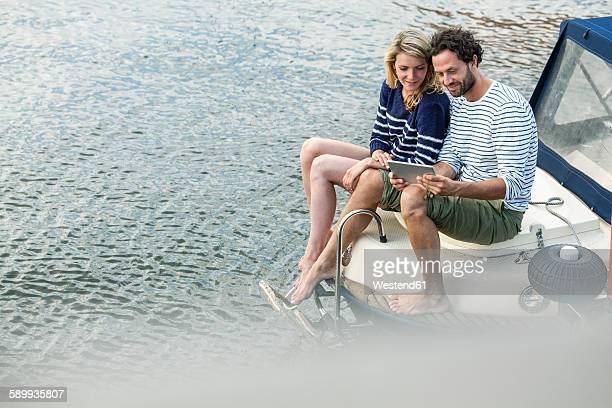 Couple on boat using digital tablet