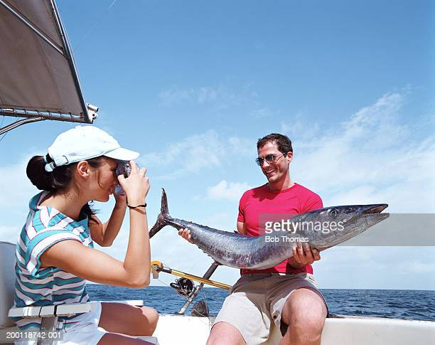 couple on boat, woman photographing man holding fish - big game fishing stock photos and pictures