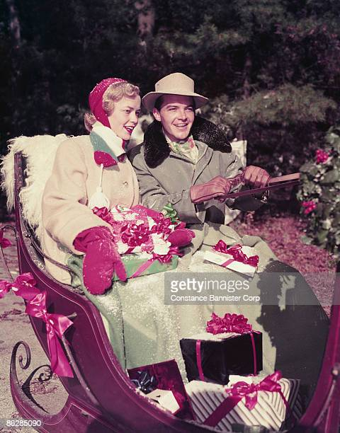 couple on christmas sleigh ride - constance bannister stock photos and pictures