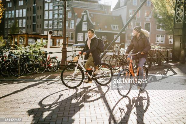 lgbt couple on city break - diverse millennial gay guys are in relationship and spending time on city break - amsterdam stock pictures, royalty-free photos & images