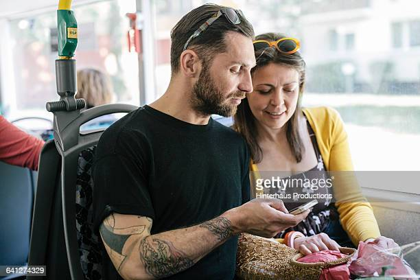 Couple on City Bus using Mobile Phone