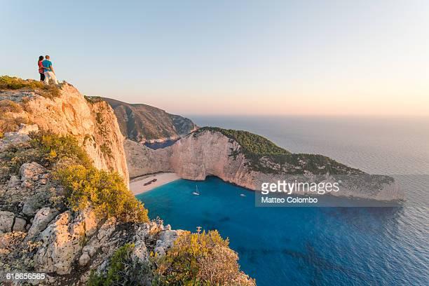 Couple on cliff, Navagio shipwreck beach. Greece