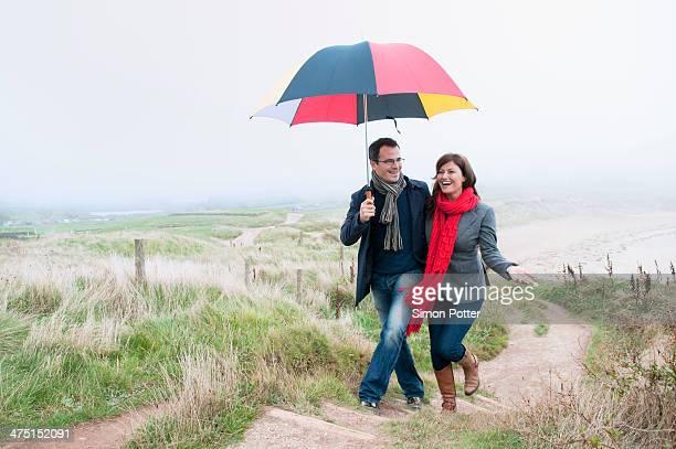 Couple on coast walk carrying umbrella, Thurlestone, Devon, UK