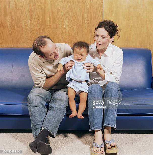 Couple on couch holding crying adopted baby girl (9-12 months)