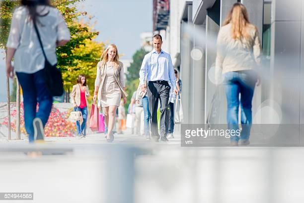 couple on crowded city street after shopping - pedestrian zone stock pictures, royalty-free photos & images