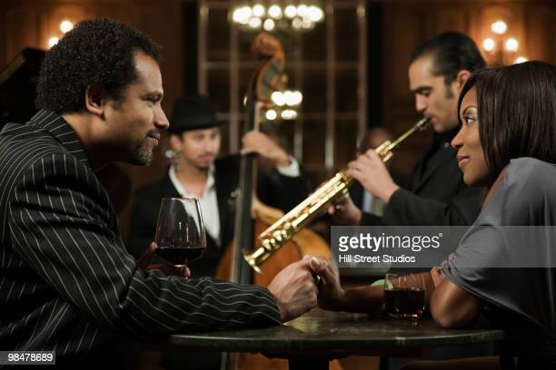 couple on date listening to jazz musicians in nightclub - fabolous musician stock photos and pictures