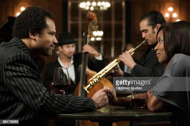 Couple on date listening to jazz musicians in nightclub