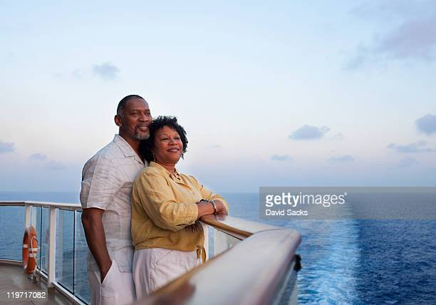 couple on deck with cruise ship wake behind them - cruise ship stock pictures, royalty-free photos & images