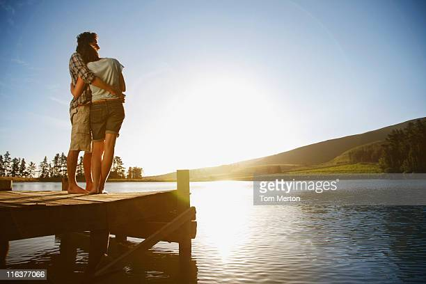 Couple on dock hugging and watching sun set over lake