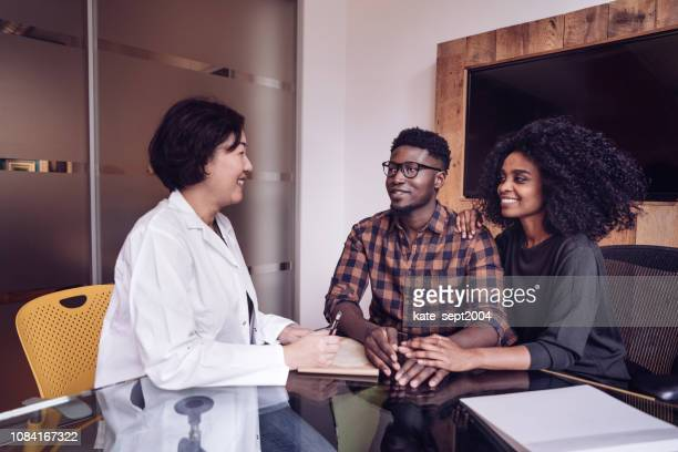 couple on doctors consultation - human fertility stock pictures, royalty-free photos & images