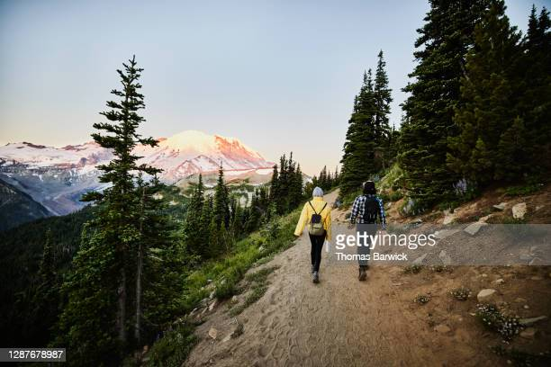 couple on early morning hike with mt rainier in background - back stock pictures, royalty-free photos & images