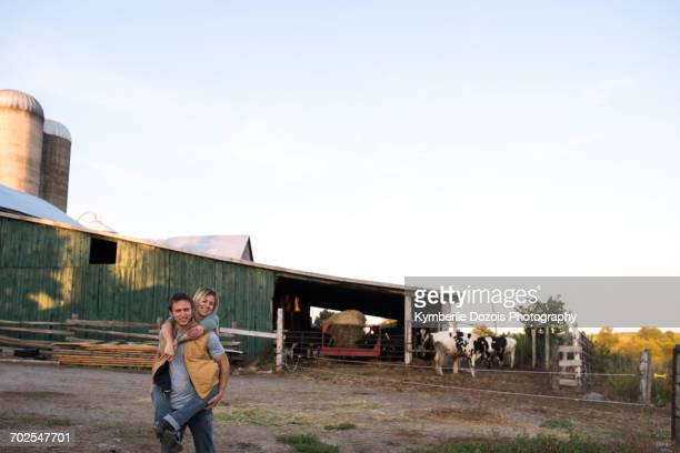 Couple on farm, man carrying woman on back
