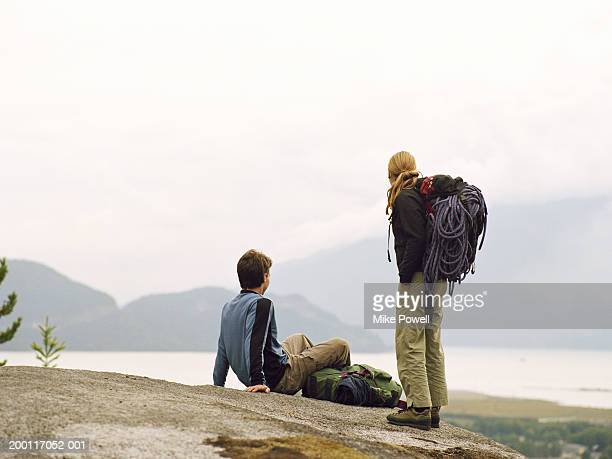 Couple on hike, resting on rock with backpacks, rear view