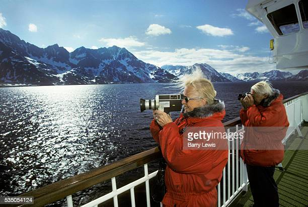 Couple on holiday filming the snowy Norwegian coast above Tromso. For more than a century, the coastal steamer Hurtigruten has been the lifeline...