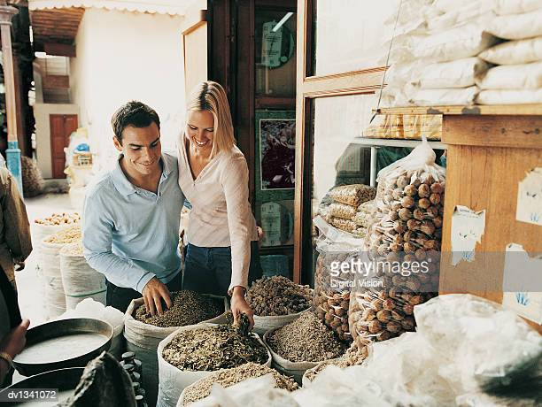 Couple on Holiday Looking Down at Sacks Full of Spices in a Market Stall at a Souk, Dubai