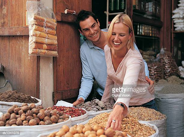 couple on holiday looking down at sacks full of spices in a market stall at a souk, dubai - souk stock pictures, royalty-free photos & images