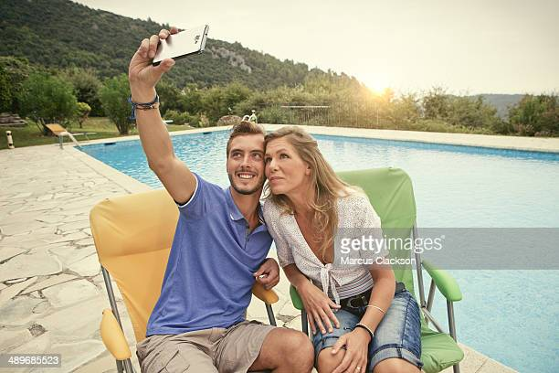 couple on holiday taking a selfie in france - older woman younger man stock photos and pictures