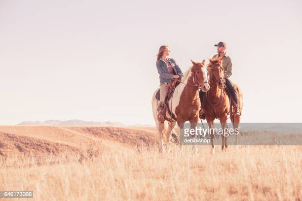 couple on horseback enjoying each other's company - istock stock pictures, royalty-free photos & images
