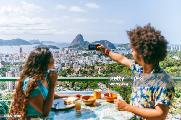 couple on hotel balcony with camera phone, rio de janeiro - hostel stock pictures, royalty-free photos & images