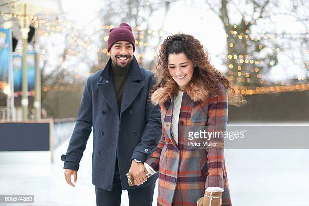 couple on ice rink holding hands smiling - スケート ストックフォトと画像