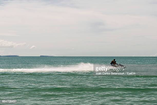 couple on jet ski at sea against sky - jet ski stock pictures, royalty-free photos & images