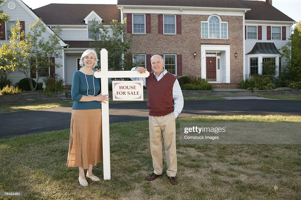 Couple on lawn of house for sale : Stockfoto
