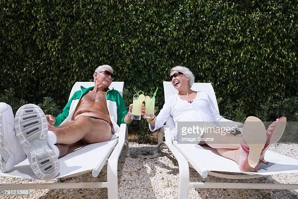 casal com espreguiçadeiras - tomando sol - fotografias e filmes do acervo