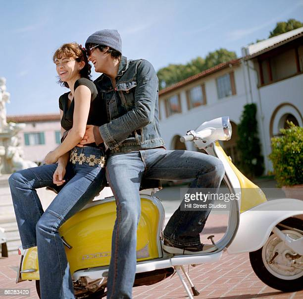 Couple on moped laughing