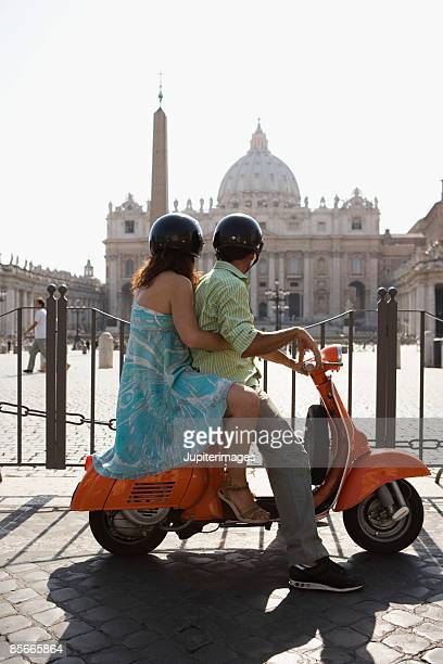 Couple on motor scooter , Saint Peter's Cathedral , Vatican City , Rome , Italy