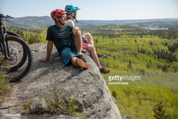 couple on mountain e-bikes relax on mountain ridge - early retirement stock pictures, royalty-free photos & images