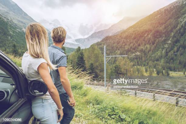 couple on mountain road contemplating the alps and glacier landscape in summer, railroad tracks. road trip concept - swiss alps stock pictures, royalty-free photos & images