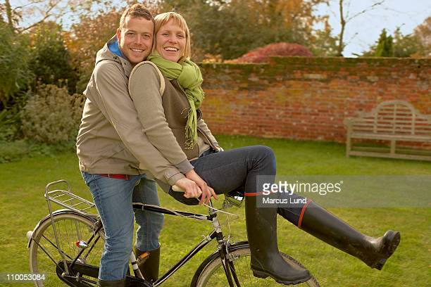 Couple on old bicycles, her on handles