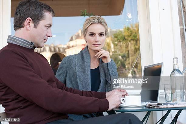 Couple sur patio extérieur avec ordinateur portable