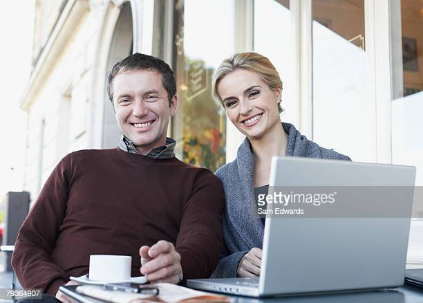 couple on outdoor patio with laptop - mid adult couple stock pictures, royalty-free photos & images