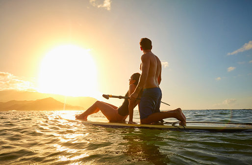 Couple on paddleboard in ocean at sunset - gettyimageskorea