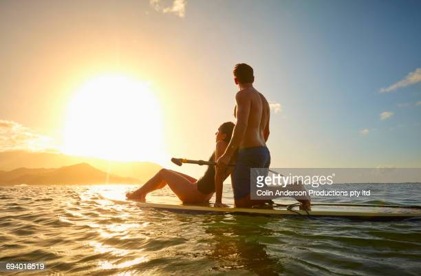 Couple on paddleboard in ocean at sunset