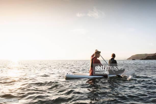 couple on paddling on paddleboard at sunset on the sea - remo atividade física - fotografias e filmes do acervo