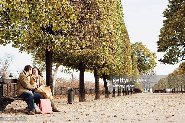 Couple on park bench with shopping bags, smiling