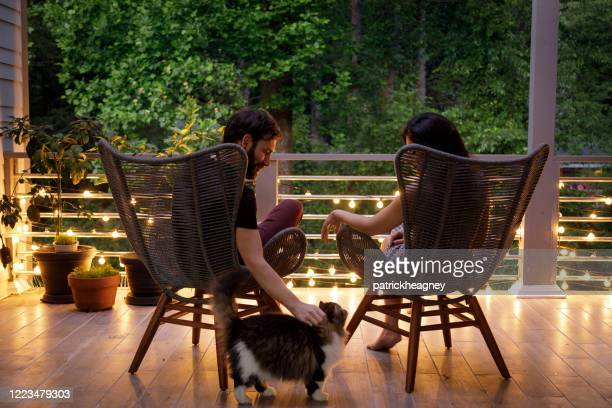 couple on patio in the evening - patio stock pictures, royalty-free photos & images
