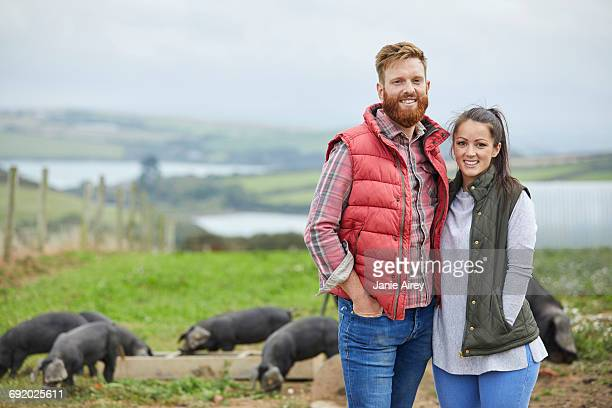 Couple on pig farm looking at camera smiling
