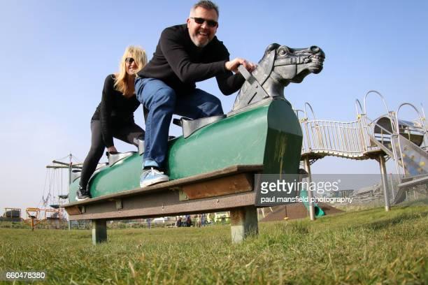Couple on playground horse ride