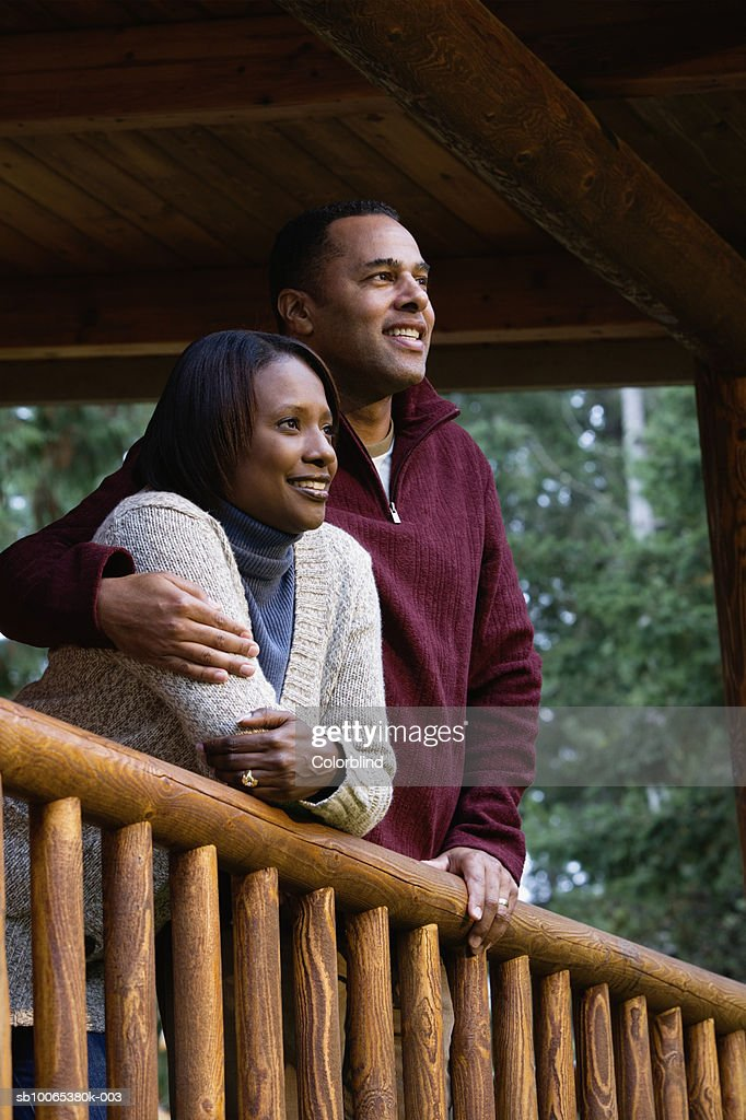 Couple on porch, looking at view, smiling : Foto stock