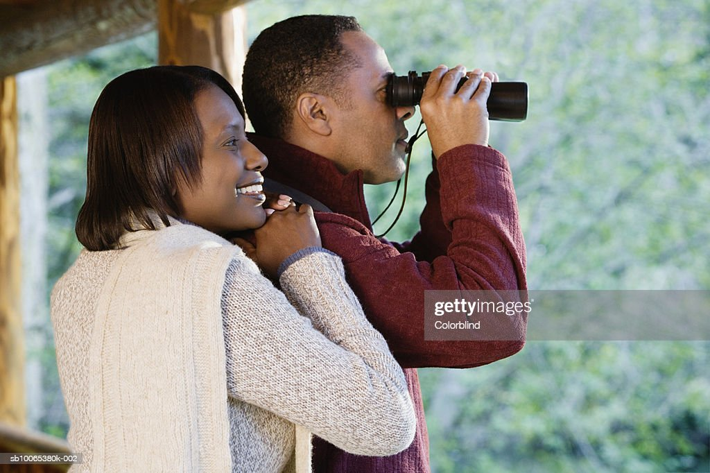 Couple on porch, man looking through binoculars, side view : Foto stock