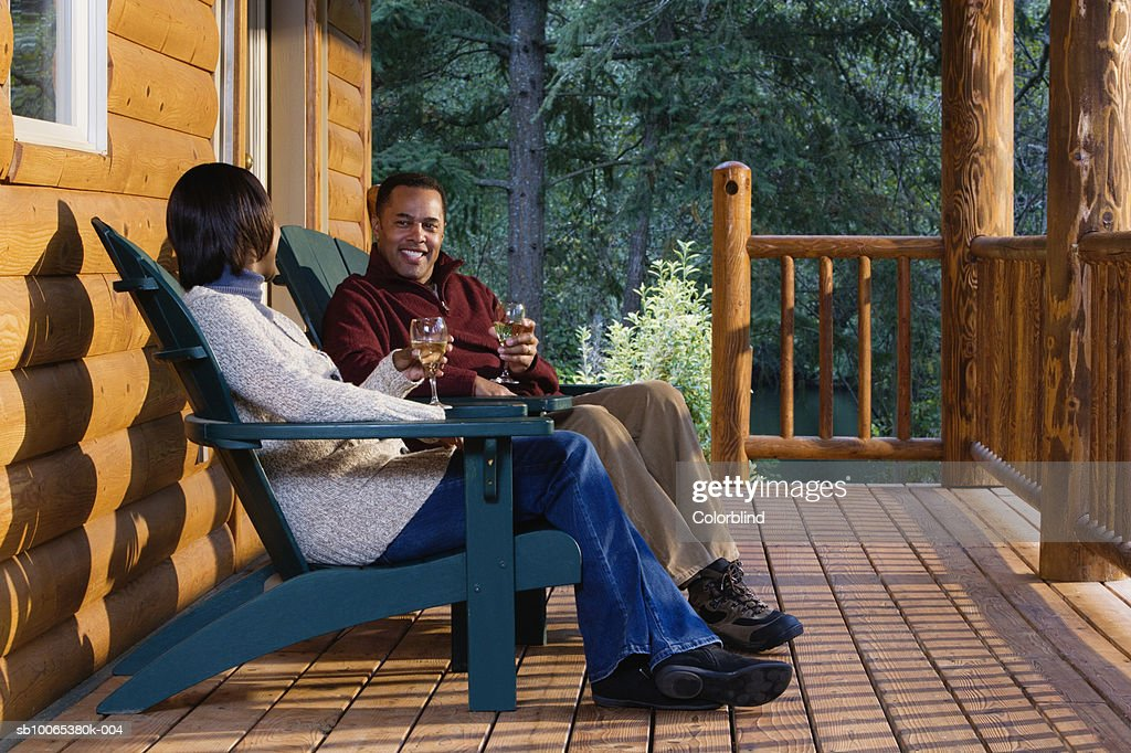 Couple on porch sitting in Adirondack chairs, drinking wine : Foto stock