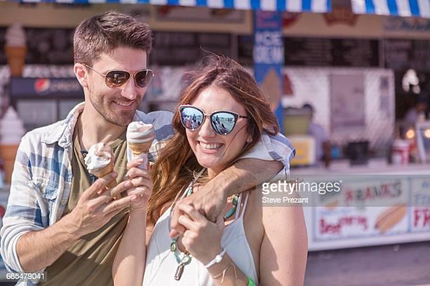 Couple on promenade holding ice cream cones smiling, Coney island, Brooklyn, New York, USA