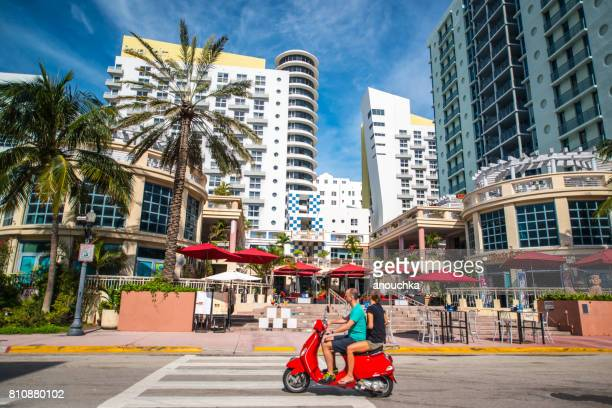 couple on red vespa driving on south beach, miami beach, usa - vespa brand name stock pictures, royalty-free photos & images