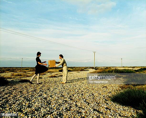 Couple on road in landscape, man passing box to woman