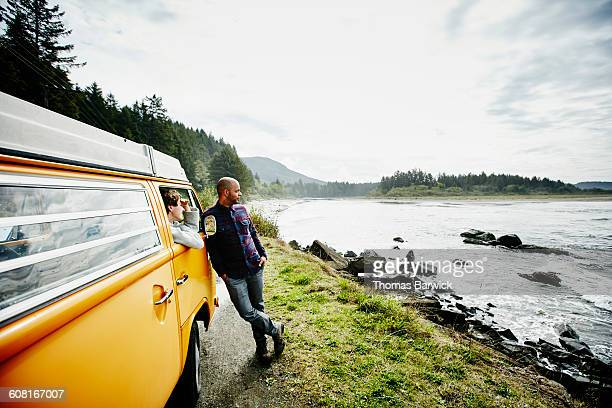 Couple on road trip in van parked by ocean