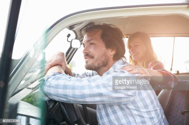 Couple on road trip sitting in car.
