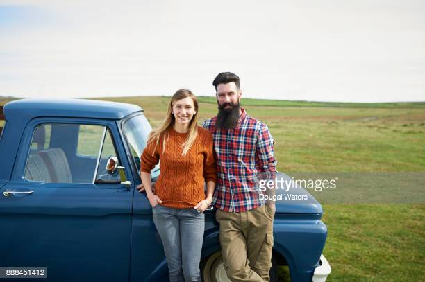 Couple on road trip standing beside truck in countryside.